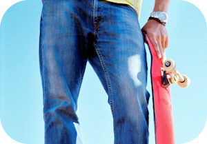 Low section of a male skateboarder holding his skateboard